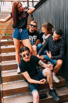 Gruppe freunde, die auf hölzernem treppenhaus sitzen
