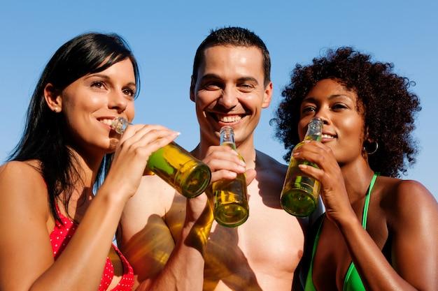 Gruppe freunde, die bier in der badebekleidung trinken