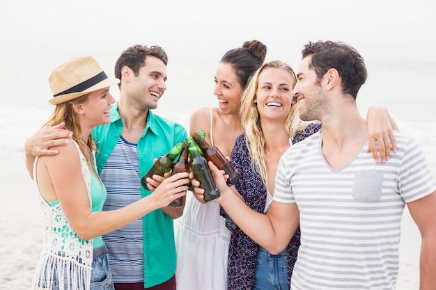 Gruppe freunde, die bierflaschen auf dem strand rösten