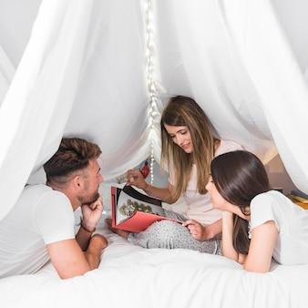 Gruppe freunde, die das fotoalbum sitzt auf bett unter dem weißen vorhang betrachten