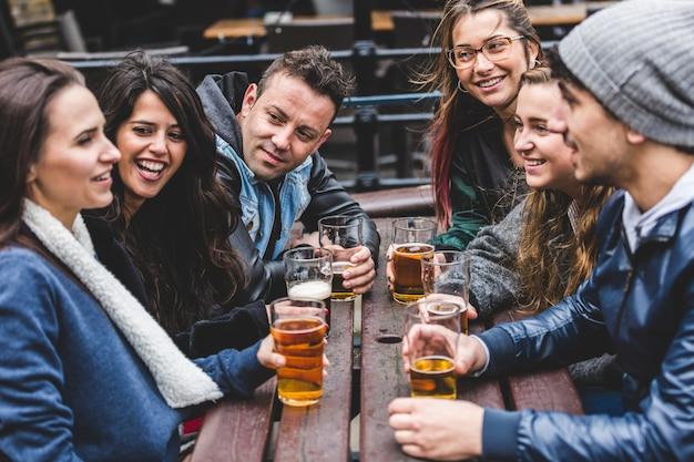 Gruppe freunde, die ein bier an der kneipe in london genießen