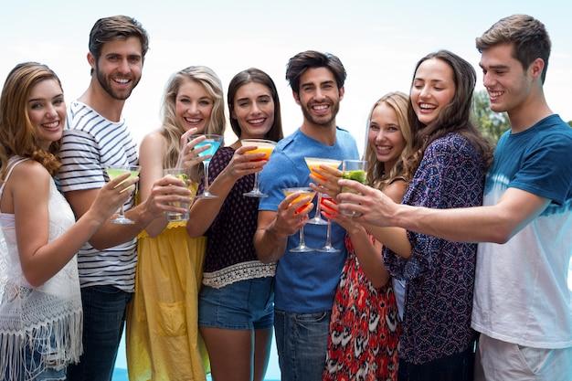 Gruppe freunde, die ein glas cocktail nahe dem pool halten
