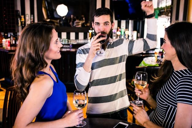 Gruppe freunde, die ein glas wein in einer bar essen