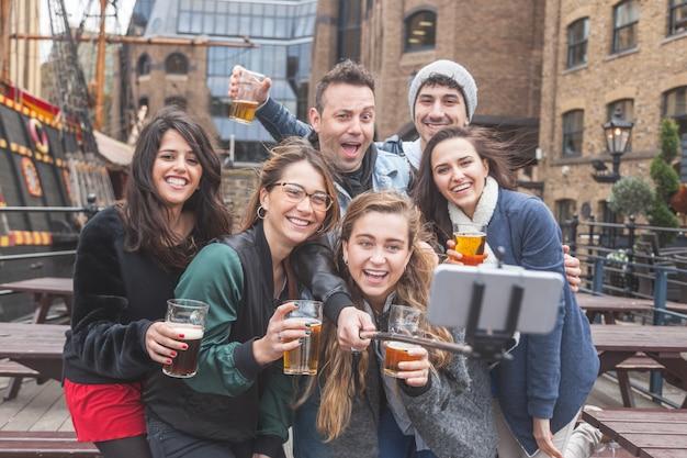 Gruppe freunde, die ein selfie an der kneipe in london nehmen