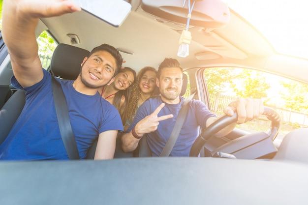 Gruppe freunde, die ein selfie in das auto nehmen