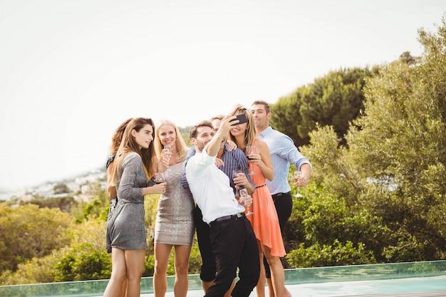 Gruppe freunde, die ein selfie nahe dem swimmingpool in einem erholungsort nehmen