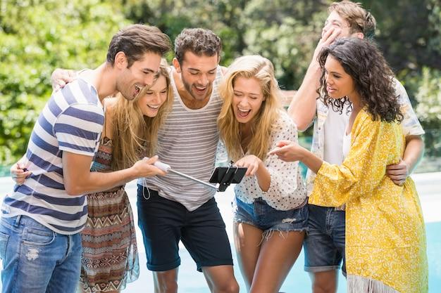 Gruppe freunde, die ein selfie nahe pool nehmen