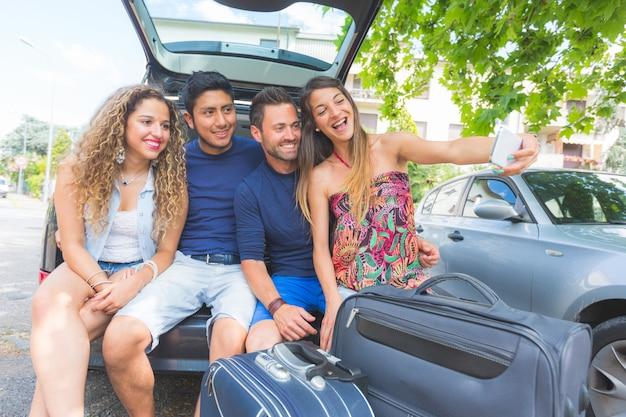 Gruppe freunde, die ein selfie nehmen, bevor sie in ferien gehen