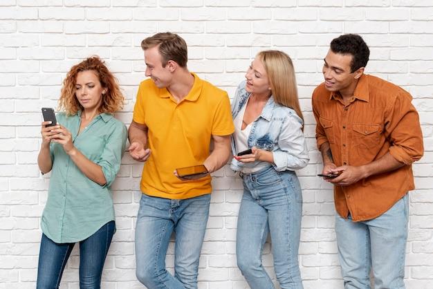 Gruppe freunde, die ein telefon überprüfen