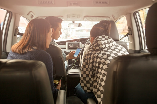 Gruppe freunde, die eine karte am handy im autostraßenreisekonzept schauen.