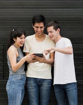 Gruppe freunde, die eine tablette überprüfen