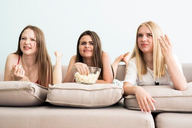Gruppe freunde, die einem film verwirrt betrachten