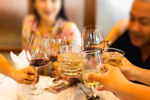Gruppe freunde, die einen toast mit gläsern rotwein und whisky anheben