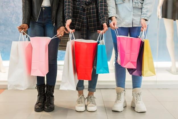 Gruppe freunde, die einkaufstaschen halten