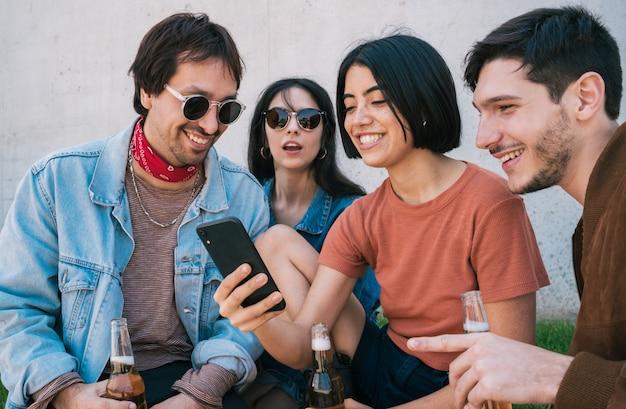 Gruppe freunde, die etwas im smartphone aufpassen.