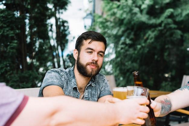 Gruppe freunde, die glas alkoholische getränke zujubeln