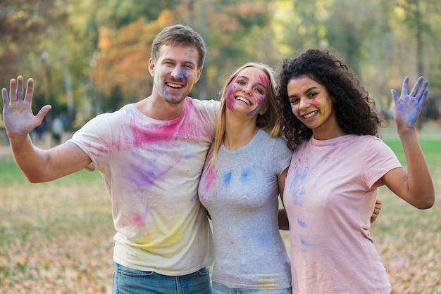 Gruppe freunde, die ihre farbigen hände wellenartig bewegen