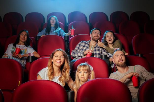 Gruppe freunde, die im kino mit popcorn und getränken sitzen