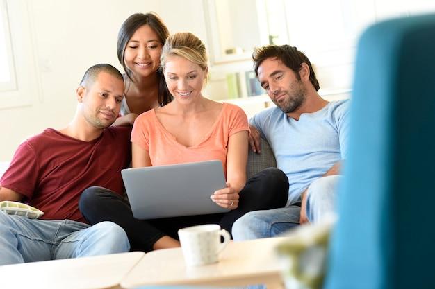 Gruppe freunde, die in der couch websurfing auf internet sitzen