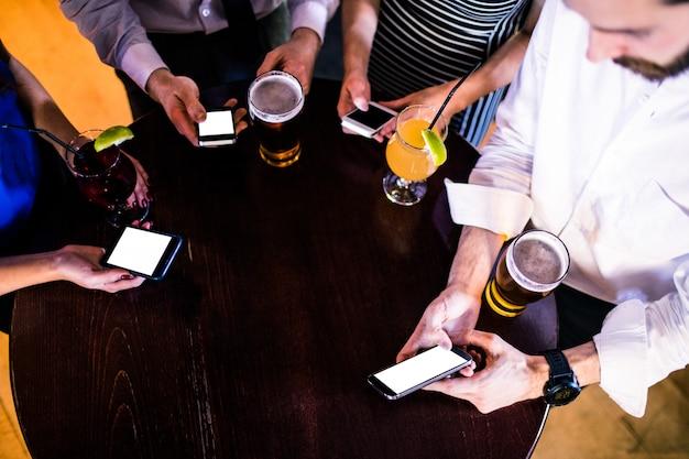 Gruppe freunde, die in einer bar simsen und etwas trinken