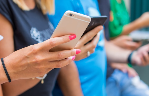 Gruppe freunde, die intelligente handys - millennials-generation aufpassen