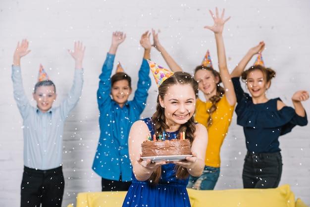 Gruppe freunde, die konfetti über dem geburtstagsmädchen halten, das geburtstagskuchen hält