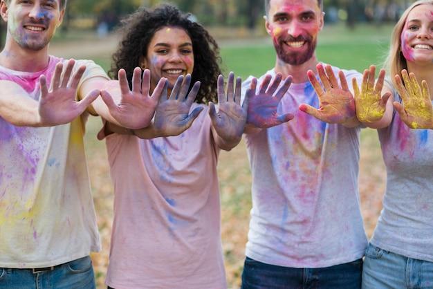 Gruppe freunde, die mit den farbigen händen am holi aufwerfen