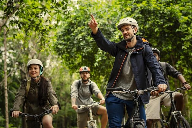 Gruppe freunde, die mountainbike im wald reiten