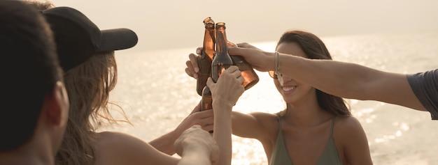 Gruppe freunde, die party claging bierflaschen am strand haben