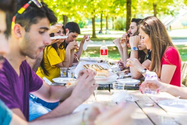 Gruppe freunde, die picknick am park haben