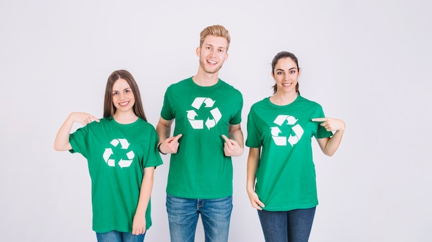 Gruppe freunde, die recycling-ikone auf ihrem grünen t-shirt zeigen