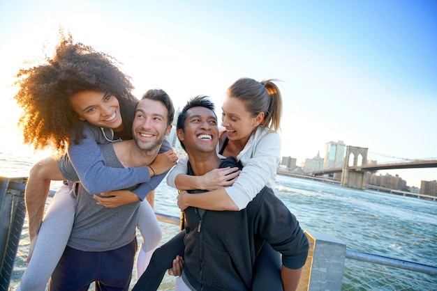 Gruppe freunde, die sonnenuntergang auf brooklyn-höhenpromenade, nyc genießen