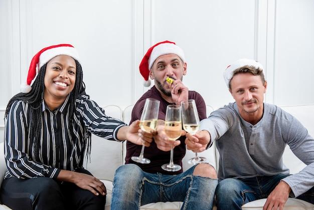 Gruppe freunde, die zu hause weihnachten feiern