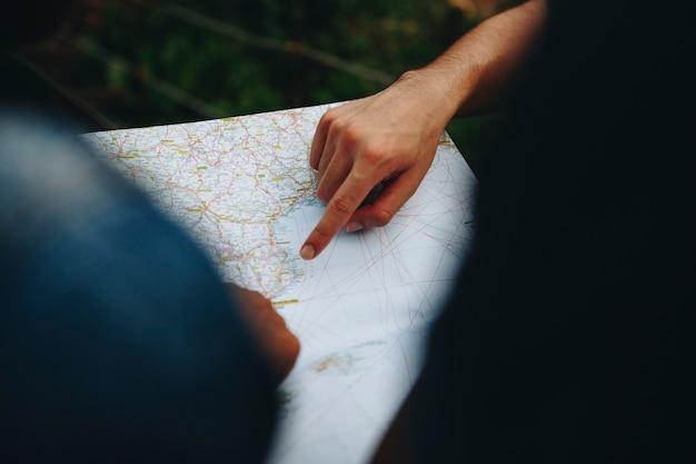 Gruppe freunde, die zusammen ein reise- und teamwork-konzept der karte betrachten
