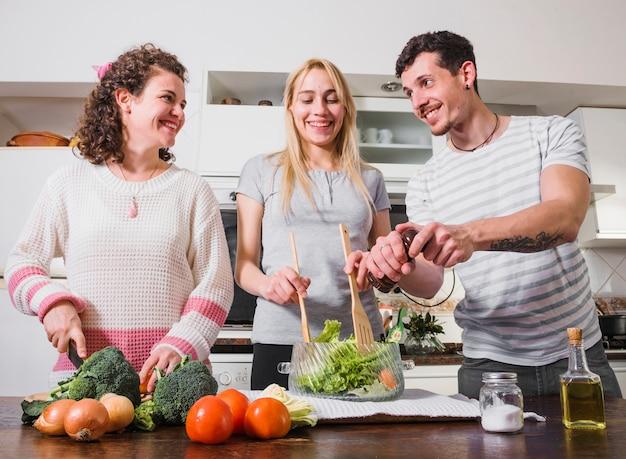 Gruppe freunde, die zusammen frischgemüsesalat in der küche machen
