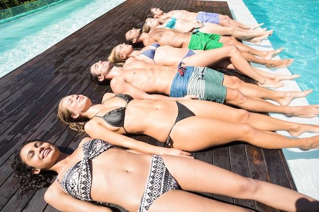 Gruppe freunde in der badebekleidung, die am poolside sich entspannt