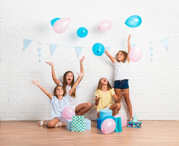 Gruppe freunde in einer geburtstagsfeier, die mit ballonen spielt