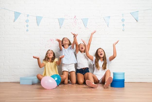 Gruppe freunde in einer geburtstagsfeier, die mit konfetti spielt