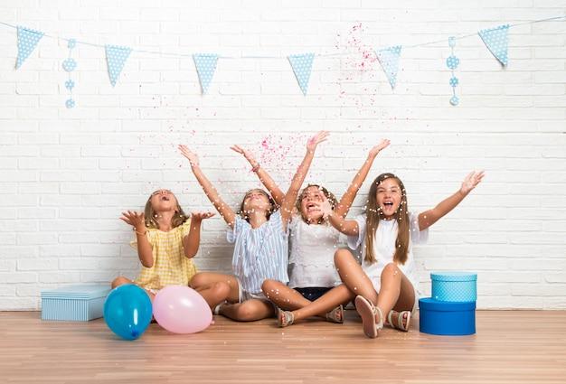 Gruppe freunde in einer geburtstagsfeier, die mit konfettis spielt