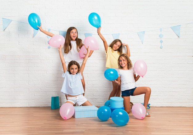 Gruppe freunde in einer geburtstagsfeier, welche die sieggeste spielt mit ballonen macht