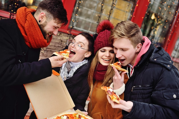 Gruppe freunde mit einem kasten pizza lächelnd und pizza auf der straße essend