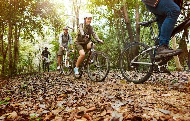 Gruppe freunde reiten mountainbike im wald zusammen