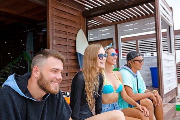 Gruppe freunde, welche die badebekleidung sitzt mit surfbrettern auf strand tragen