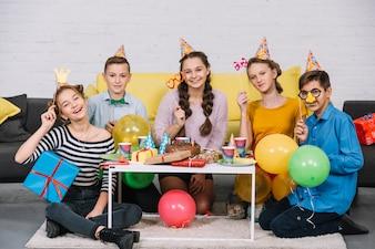 Gruppe Freunde, welche die Stütze die Geburtstagsfeier genießen genießen