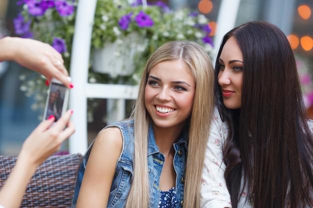 Gruppe freundinnen, die ein selfie foto an der beweglichen kamera ein lächeln machen. hübsche frauen, die spaß am café haben. junge mädchen lachen