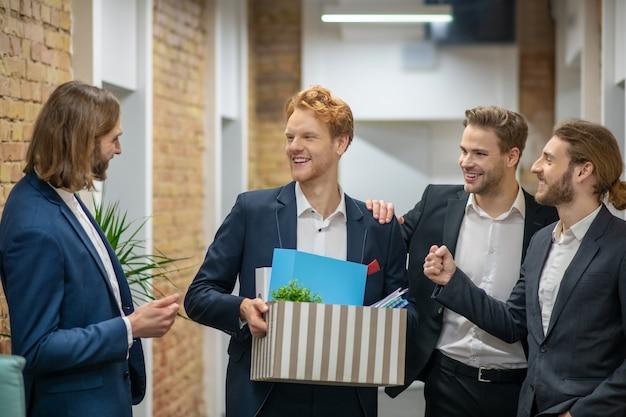 Gruppe fröhlich gut aussehender junger männer in anzügen, die freudig im bürokorridor sprechen