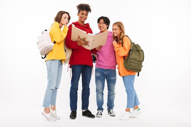 Gruppe fröhliche teenager isoliert, rucksäcke tragend, einen offenen ordner betrachtend