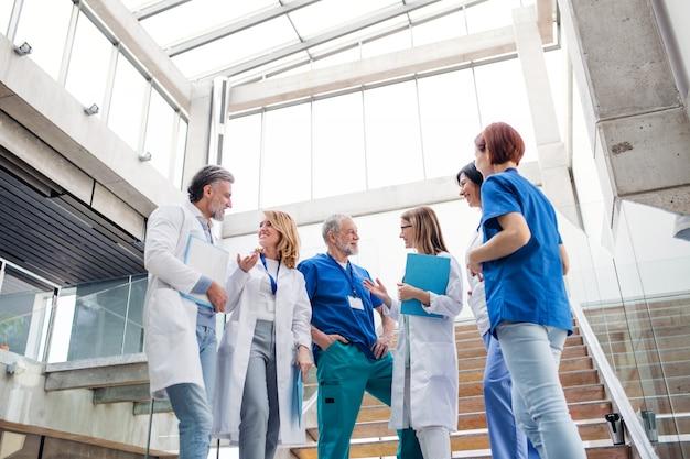 Gruppe fröhlicher ärzte, die auf der medizinischen konferenz des treppenhauses stehen und sprechen.