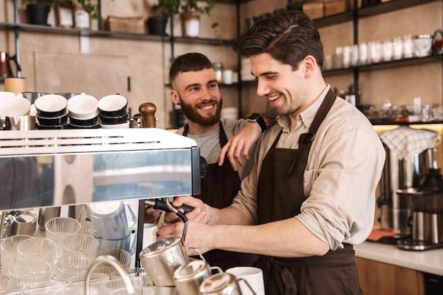 Gruppe fröhlicher baristas, die schürzen tragen, die an der theke im café drinnen arbeiten und sprechen