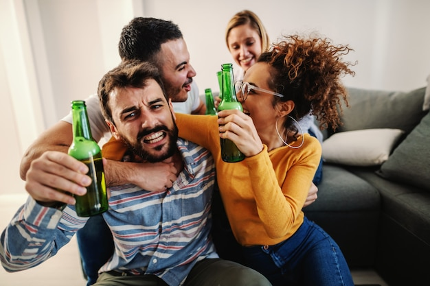 Gruppe fröhlicher freunde, die zu hause sitzen und fußballspiel im fernsehen schauen. ihre lieblingsmannschaft gewinnt.